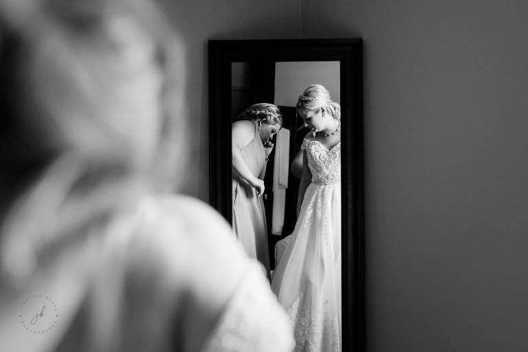 A bride seeks an opinion from her friend and bridesmaid after she has put on her wedding dress and is assessing it in the mirror.