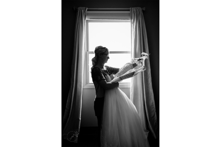 A bride admires her gown, hanging on a whimsical hanger with her married name, before she dons the dress.