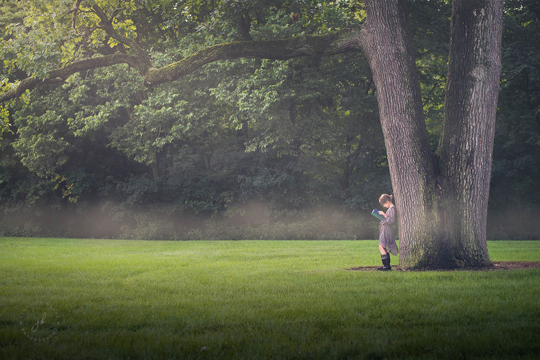A girl leans against a large tree on a foggy morning as she reads a book.